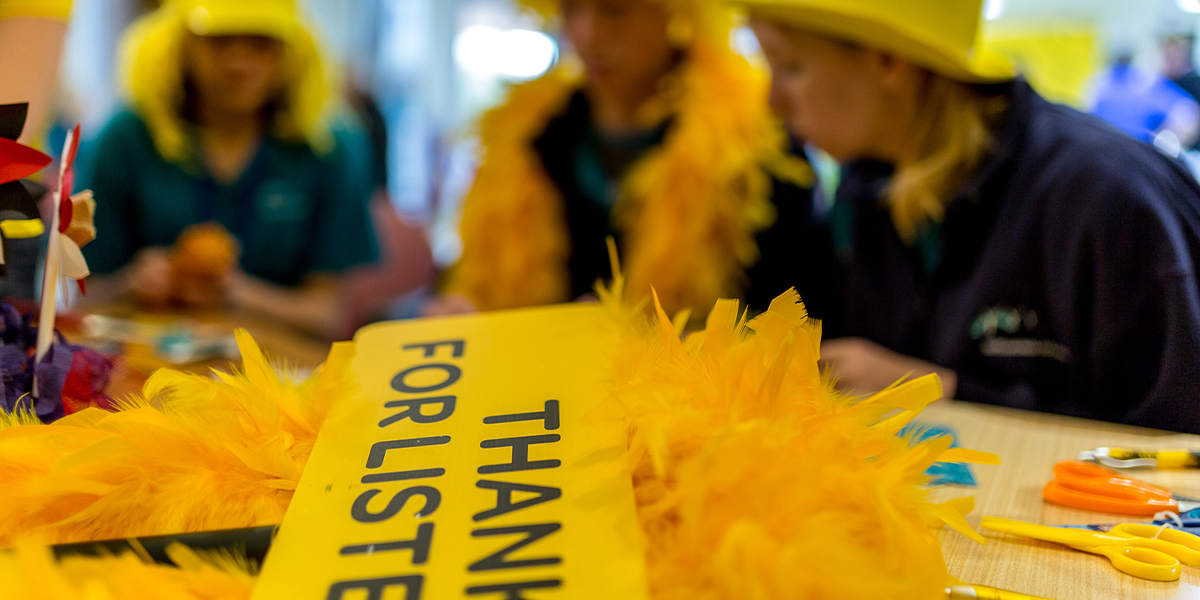 A group busy themselves with yellow clothing and signs to raise funds and awareness for R U OK?